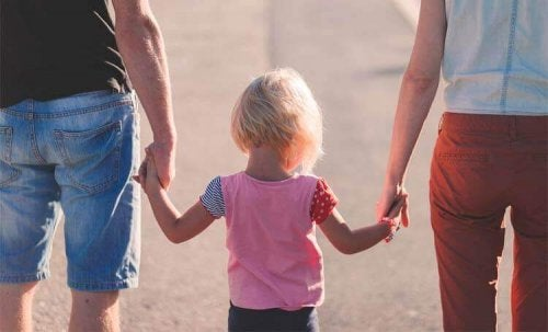 Child holding her parents' hands.