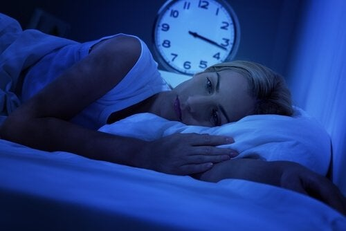 Woman in bed wakes up in bed in the middle of the night.
