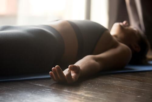 A woman practicing mindfulness lying down on the floor in a state of relaxation.