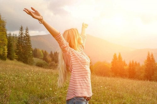 A woman with open arms greeting the day.