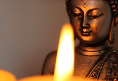 A Buddha statue in front of a candle flame.