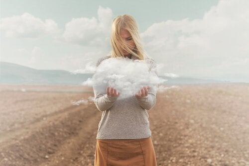 A blonde woman standing in a barren field holding a small cloud.