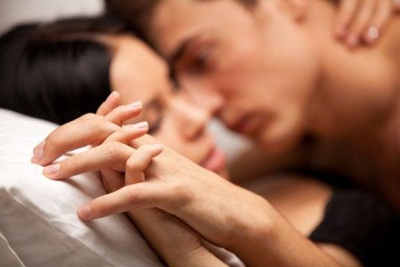 kvinde og mand i seng der fletter fingre