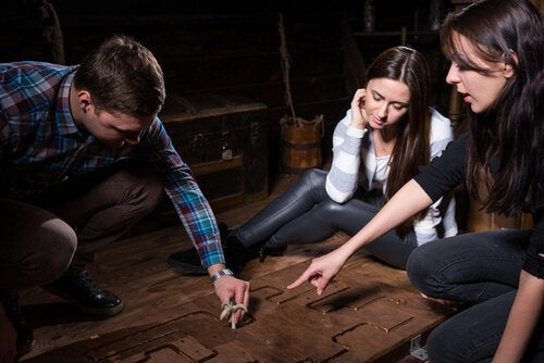 A man and two women working together to solve a puzzle on the floor of an escape room.