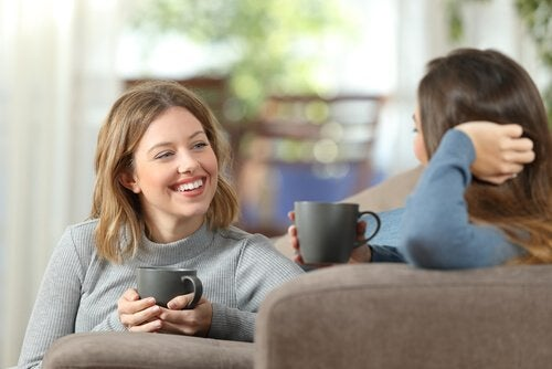 Two girlfriends laughing and drinking coffee.