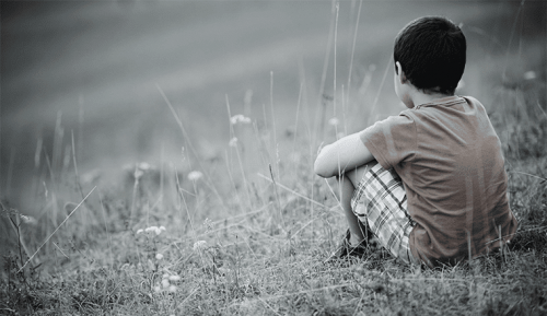 A child sitting on the ground by himself.