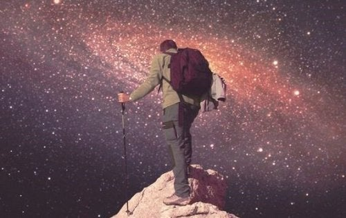 A man climbing to the top of a mountain under the starry sky.