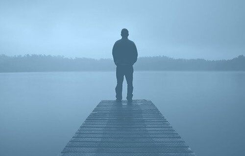 A man on a dock in the mist.