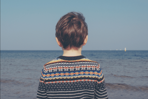 A grieving child looking out at the ocean.