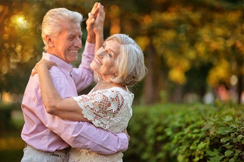 An older man and woman dancing together with smiles on their faces.