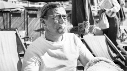 Jean-Paul Sartre sitting in a beach chair.