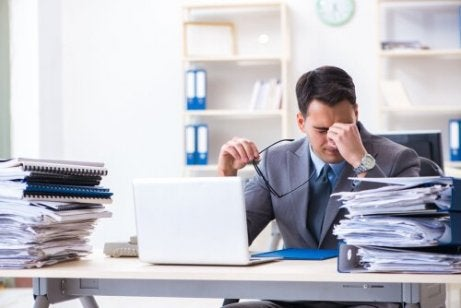 A stressed man at his desk working.
