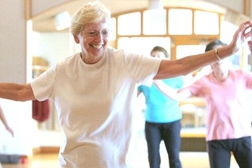 An older woman dancing with a smile on her face.