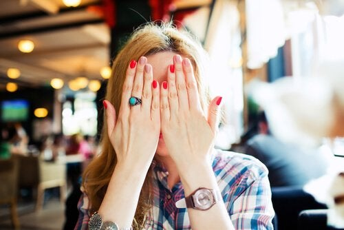 Woman hiding her face in shame.
