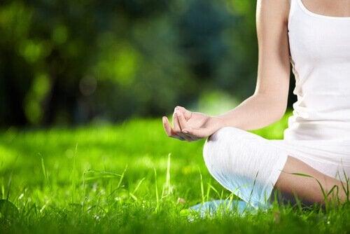 Kobieta medytuje w trawie.