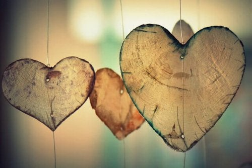 Three wooden hearts hanging on string.