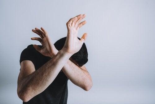 mand der beskytter sig med sine arme