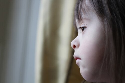 A girl with Down syndrome looking out the window.