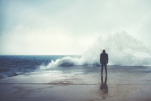 A guy watching a wave break on a pier.
