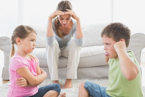 Children arguing in front of a frustrated caregiver.