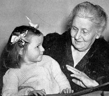 Maria Montessori talking to a little girl.