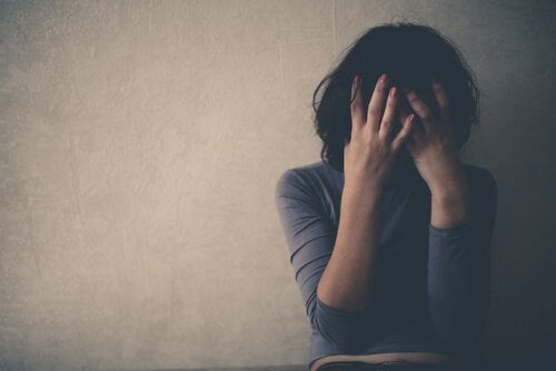 A depressed woman covering her face in front of a wall.