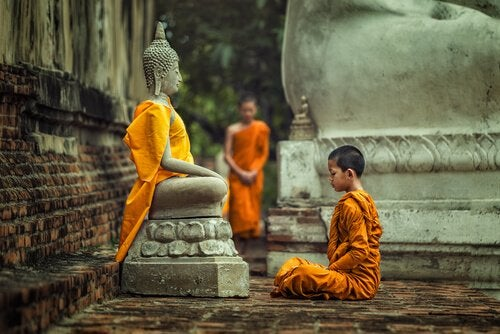 A boy sitting front of a statue of Buddha.
