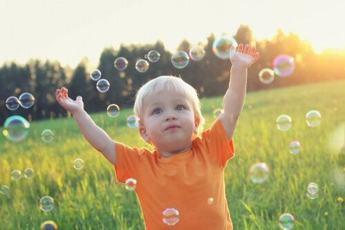 A boy playing with soap bubbles in a field.