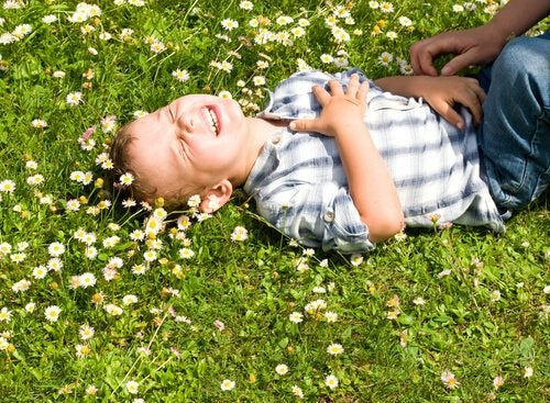 A boy in a field laughing due to a Gianni Rodari quote.