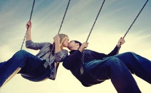 A couple kissing on some swings.