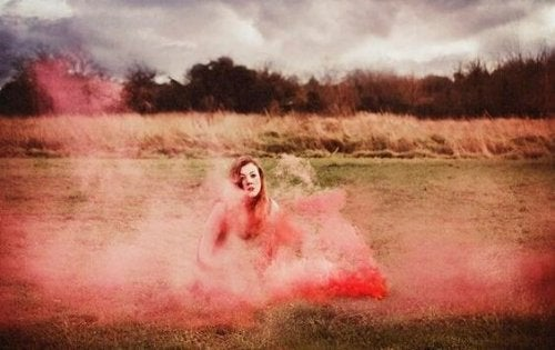 A woman in a field surrounded by pink smoke.