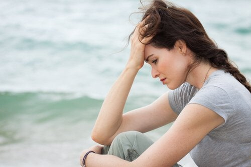 A worried woman sitting near the sea.