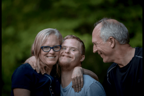 Two older adults and a young man with Down syndrome.