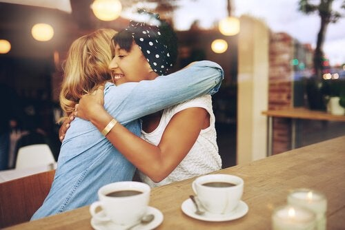 Friends hugging at a café.