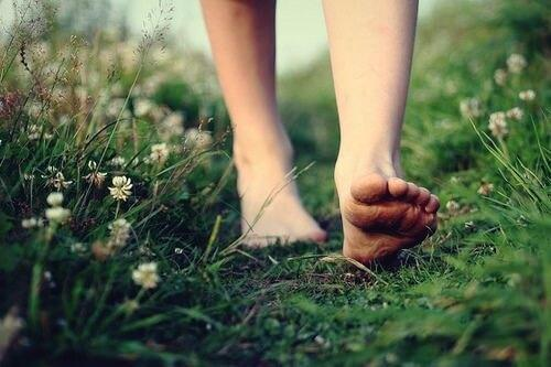A picture showing someone from the calves down, walking barefoot in the grass.