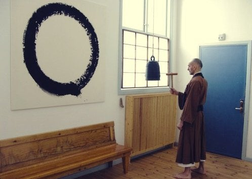 A Buddhist monk staring at an ensō circle on a wall.