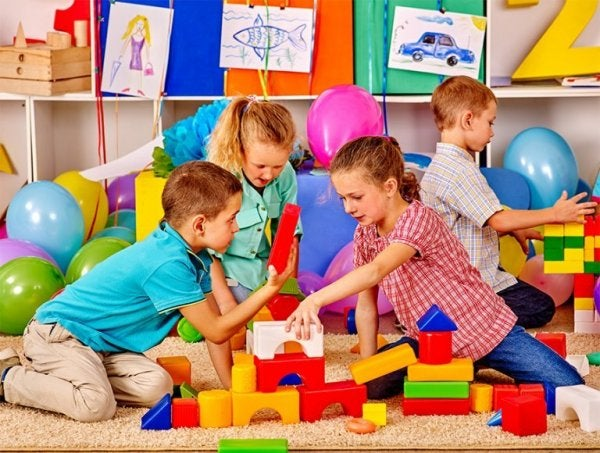 A group of children playing with large, colorful building blocks.