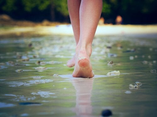 A photo showing a pair of feet walking along a road covered in a thin layer of water.