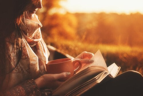 A woman reading biographies during sunset.