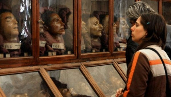 A couple standing in front of a series of glass display cases with replicas of human heads in them.