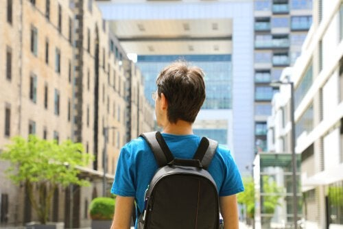 A man wearing a backpack, looking out onto a city street.