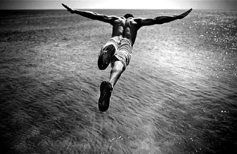 A man with neophilia diving into the ocean.