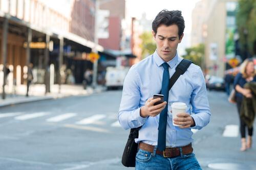 A man in a shirt and tie walking down the street with a coffee in one hand and his phone in another.