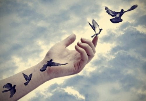 A hand with flying birds.