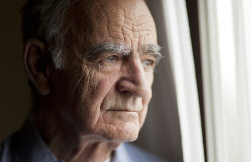An old man looking out the window of a nursing home.