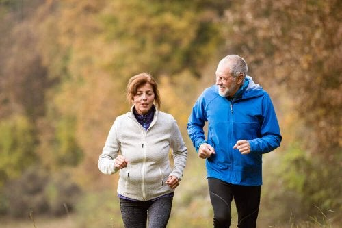 Two older people jogging together.