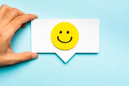 A business card with a smiley face on it, representing emotional branding.