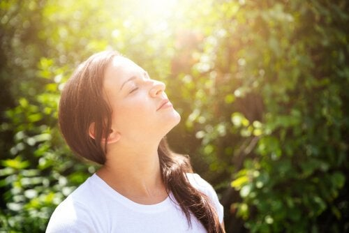 A picture showing a woman looking up with her eyes closed and taking in the nature around her.