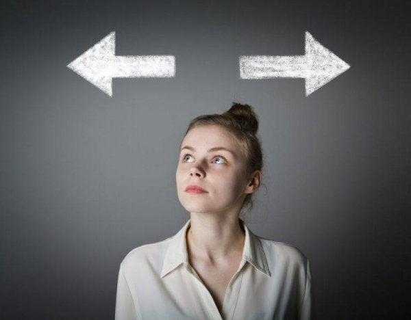 A woman looking up at two arrows as she tries to decide which way to go, symbolizing rational choice theory.