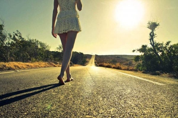 A woman walking barefoot in the middle of a country road.